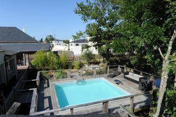 Parfaitement carrée, la piscine est installée sur une terrasse en bois