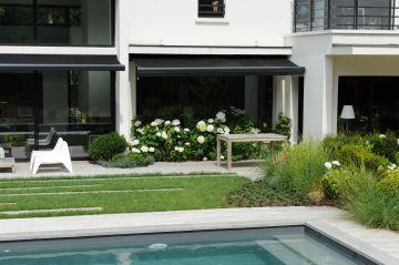 Les margelles de la piscine viennent rappeler le blanc de la maison