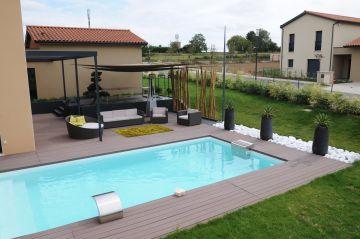 Une piscine à proximité d'un salon de jardin