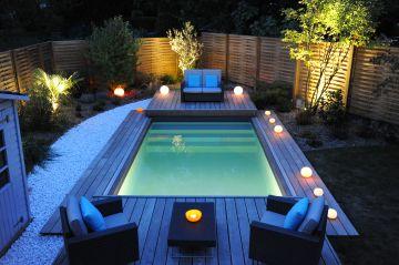 La piscine et son Rolling-Deck ouvert à la tombée du jour et entourée de bougies d'ambiance.