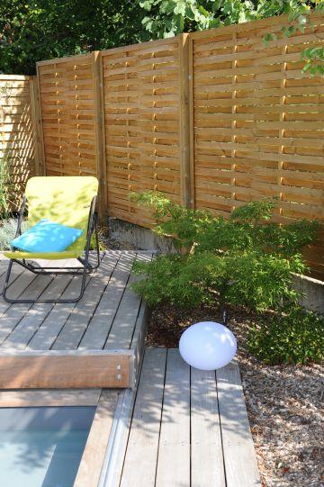Quelques végétaux et un simple bardage bois permettent de donner un esprit zen à l'ensemble.